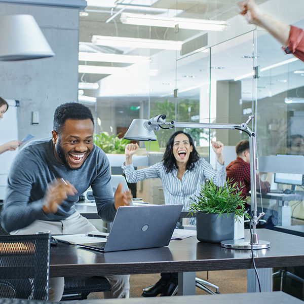 Busy Corporate Office, Man Working on a Laptop Signs Important Contract and Jumps in Celebration, Gives High-Five to His Coworkers. Everybody is Happy.
