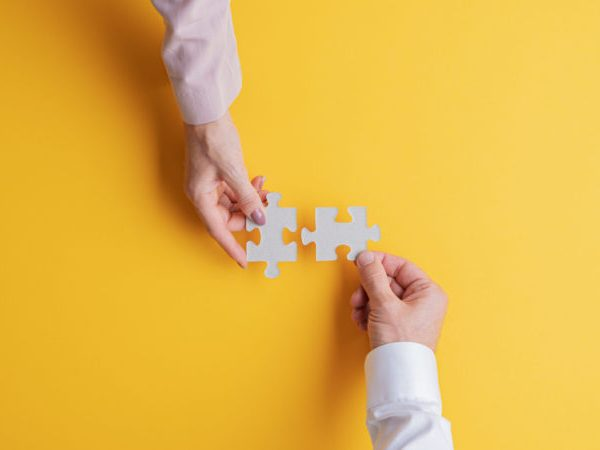 Top view of male and female hands joining two matching puzzle pieces together in a conceptual image. Over yellow background.